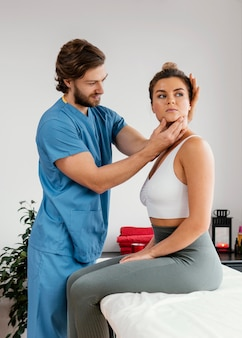 여성 환자의 목 근육을 검사하는 남성 정골 치료사