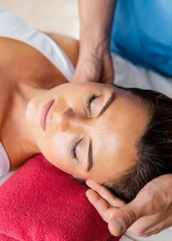 여성 환자의 목 척추를 확인하는 남성 정골 치료사