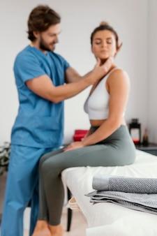 여성 환자의 목 강도를 확인하는 남성 정골 치료사
