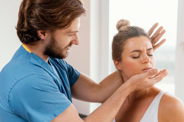 여성 환자의 목을 검사하는 남성 정골 치료사