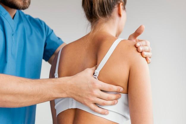 Мужской остеопатический терапевт, проверяющий лопатку пациентки