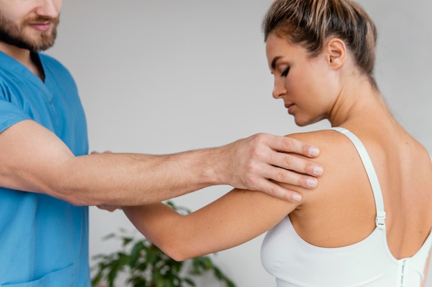 Male osteopathic therapist checking female patient's shoulder pain