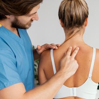 여성 환자의 척추를 검사하는 남성 정골 치료사