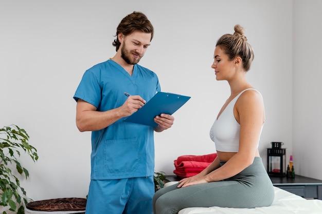병원에서 여성 환자 서명 클립 보드와 남성 정골 치료사