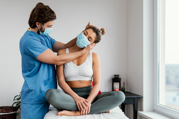 Male osteopathic therapist with medical mask checking female patient's neck muscles