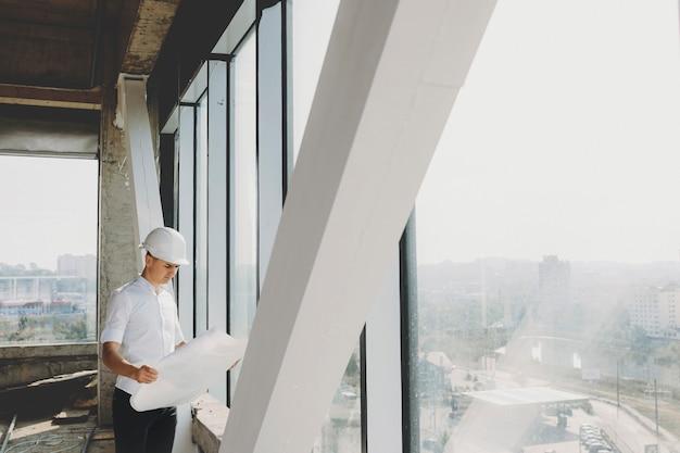 건설중인 그의 건물의 큰 창 근처에서 계획을보고있는 남성 소유자.