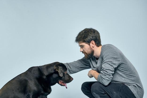 男性の飼い主はソファで犬と遊ぶ