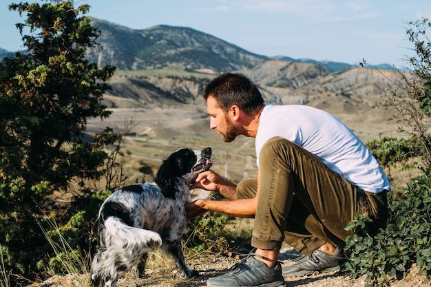 Male owner of spaniel dog walking against mountains background