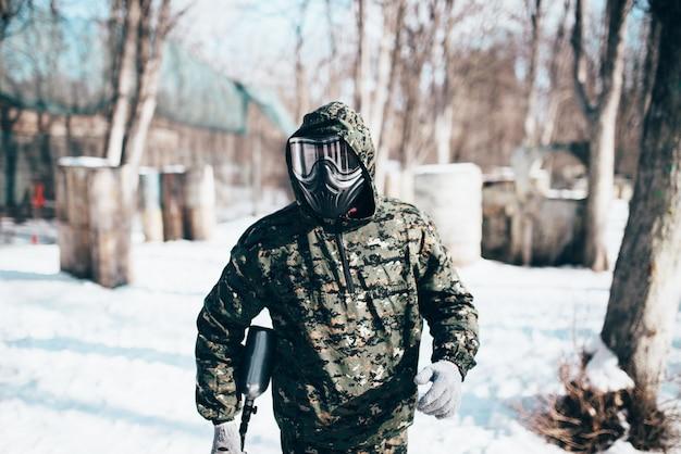 保護マスクと制服を着た男性のペイントボールプレーヤーが冬の森の戦いの前に兵士を手にマーカー銃を保持しています。エクストリームスポーツ、軍事ゲーム機器
