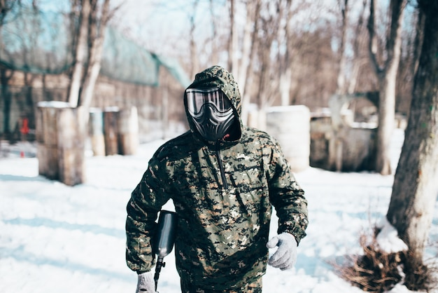 Male paintball player in protection mask and uniform holds marker gun in hands, soldier before winter forest battle. extreme sport, military game equipment