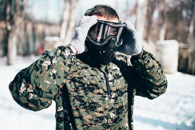 男性のペイントボールプレーヤーは、冬の森の戦いの前に保護マスクを着用します。エクストリームスポーツ、軍事ゲーム機器