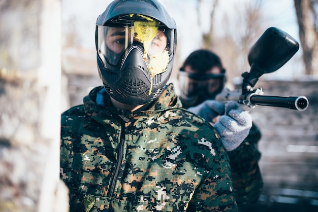 Male paintball player in splattered mask, front view, winter battle. extreme sport game, soldier in special uniform