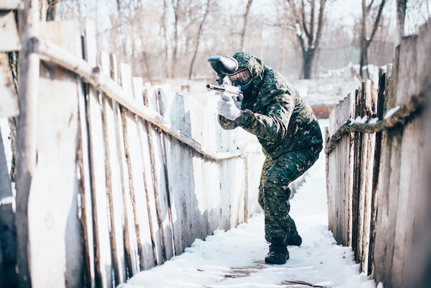 Male paintball player with marker gun in hands attack, front view, winter battle. extreme sport game, soldier fights in protection mask and uniform