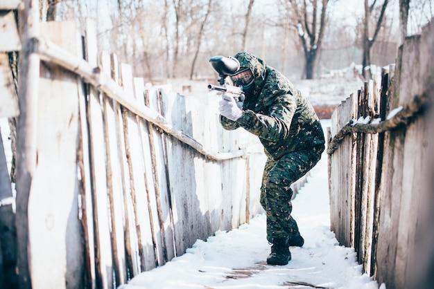 手の攻撃、正面図、冬の戦いでマーカー銃を持つ男性のペイントボールプレーヤー。エクストリームスポーツゲーム、防護マスクと制服で戦う兵士