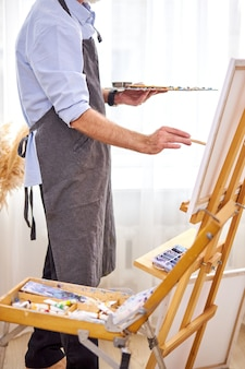 Male painter in apron making masterpiece with brush on canvas, picture on easel. design, art, craft, painting concept