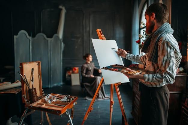 男性の画家がスタジオで女性のポーズに対して肖像画を描きます。