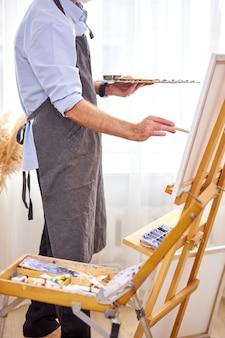 캔버스에 브러시로 걸작을 만드는 앞치마의 남성 화가, 이젤에 그림. 디자인, 예술, 공예, 회화 개념