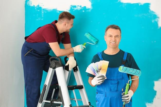 屋内でカラーパレットのサンプルとローラーブラシで制服を着た男性画家
