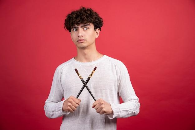 Pittore maschio che posa con le spazzole.