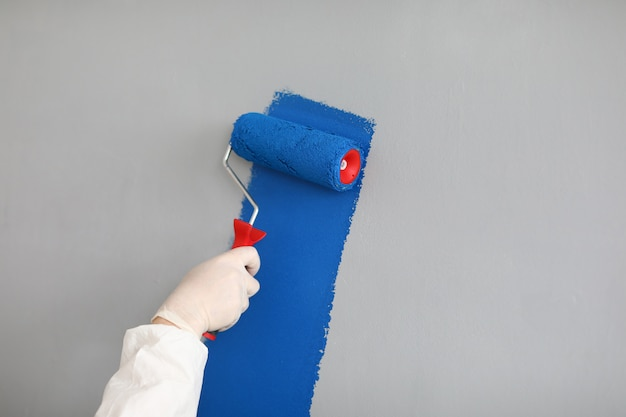 Male painter in uniform paints wall with roller