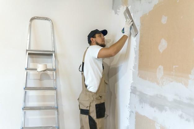 Художник-мужчина со шпателем в руках делает ремонт дома. концепция ремонта номеров.