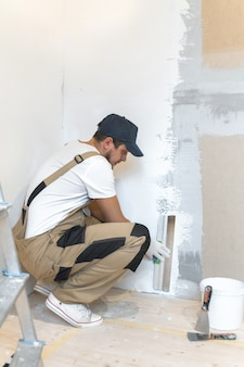Male painter with a spatula in his hands makes repairs in home. room renovation concept.