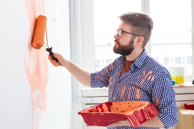 ペイントローラーで壁を塗る男性。彼女の新しいアパートで壁を描いている面白い男の肖像画