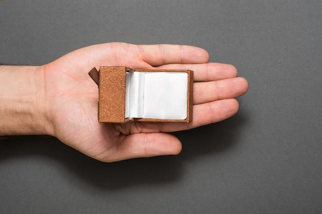 空の開いた茶色の宝石箱を持つ男性の手のひら。プレゼント。黒の背景