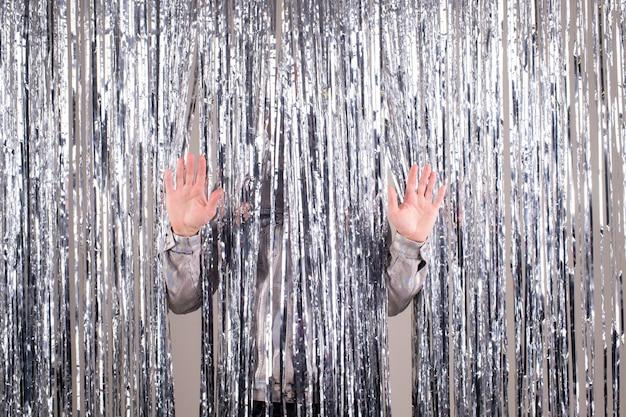 輝くきらびやかなカーテンの上の男性の手のひら