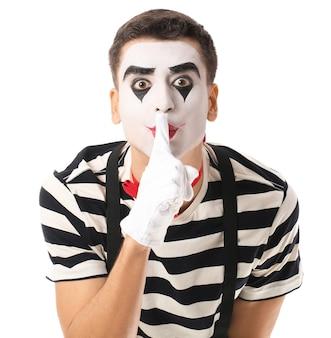 Мужской пантомимист показывает жест молчания на белом фоне