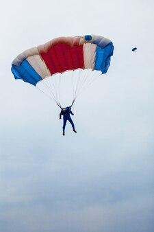 Мужчина-парашютист под разноцветным парашютом