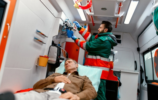 A male paramedic in uniform looks for an oxygen mask to help a senior patient lying on a gurney in a modern ambulance.