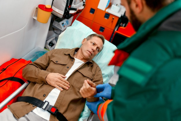 A male paramedic in uniform measures the pulse of a senior patient lying on a gurney in a modern ambulance.