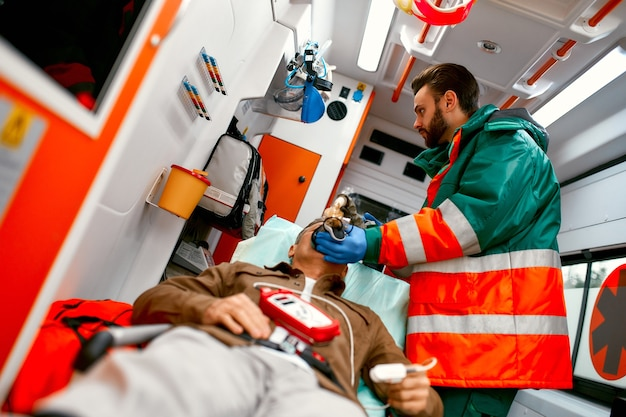 A male paramedic in uniform puts on an oxygen ventilator to help a senior patient lying on a gurney in a modern ambulance.