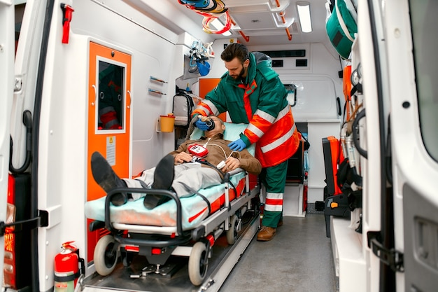 A male paramedic in uniform puts on a ventilator with oxygen to help a senior patient lying on a gurney with a pulse oximeter in a modern ambulance.