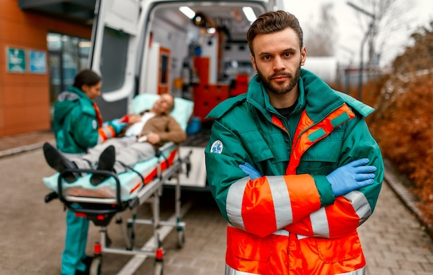 A male paramedic in uniform stands with his arms crossed in front of an ambulance and his colleague standing near a patient's gurney.