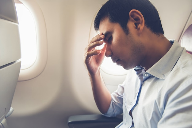 Male passenger having airsickness on the plane