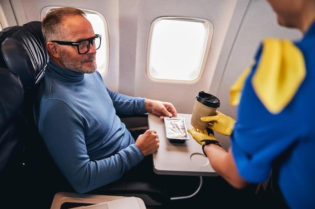 Пассажир мужского пола смотрит на бортпроводника