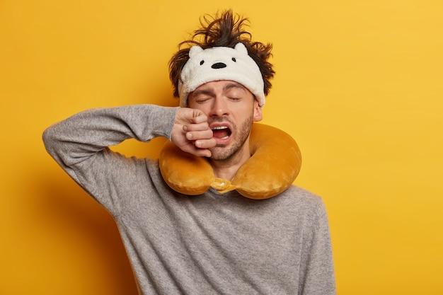Passeggero di sesso maschile che indossa un cuscino da viaggio gonfiato sul collo e una graziosa maschera per gli occhi