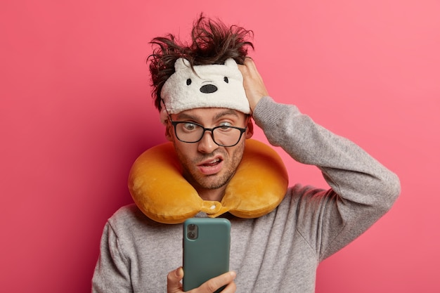 Male passenger wearing inflated travel pillow over neck and cute eye mask