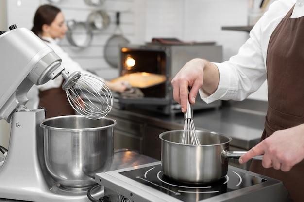 男性のパティシエは、ケーキを埋めるために鍋でベリークリを調理します。