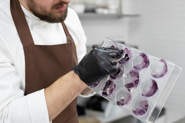 チョコレート球の型に光沢のあるカンドゥリンを適用するために手ぬぐいを使用する男性のパティシエ