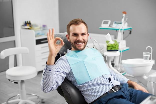 Пациент мужского пола после лечения зубов в стоматологии