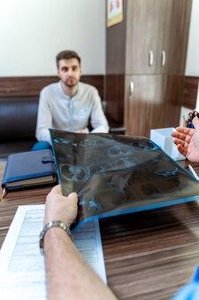 Пациент мужского пола в офисе после мрт. врач объясняет рентгеновский снимок пациенту.