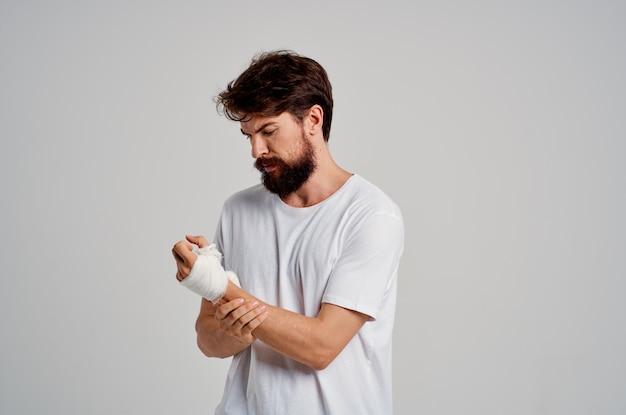 男性患者が指に包帯を巻いた手の怪我入院明るい背景