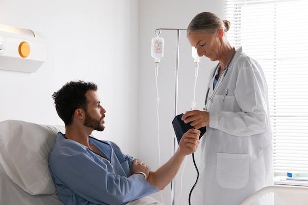 Paziente di sesso maschile a letto a parlare con un'infermiera
