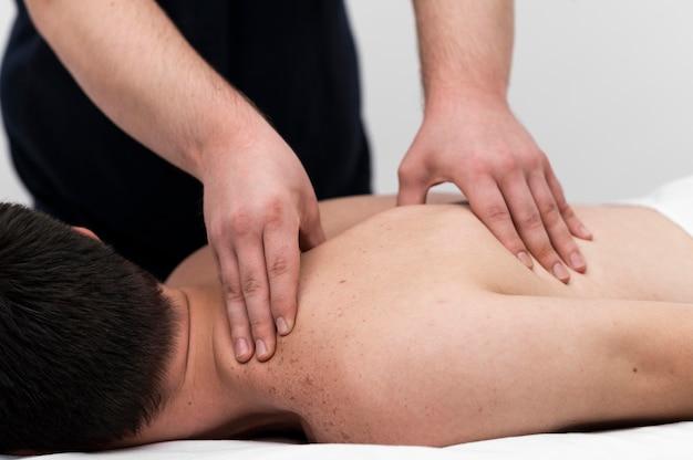 Пациенту мужского пола делает массаж спины физиотерапевтом