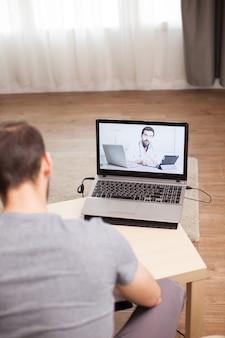 検疫中に医師とビデオ会議を行っている男性患者。