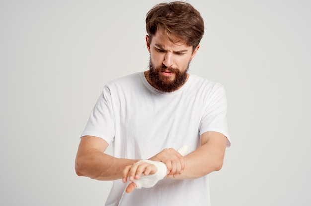 흰색 티셔츠를 입은 남성 환자는 붕대를 감고 병원 약을 포즈를 취했습니다. 고품질 사진