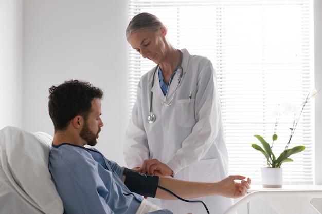 Пациент мужского пола в постели разговаривает с медсестрой